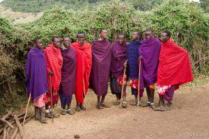 Group of Maasai men prepping for a welcome song and dance