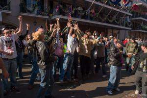 People on Bourbon Street trying to catch beads