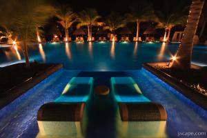 Night shot of the adult pool with sunken loungers